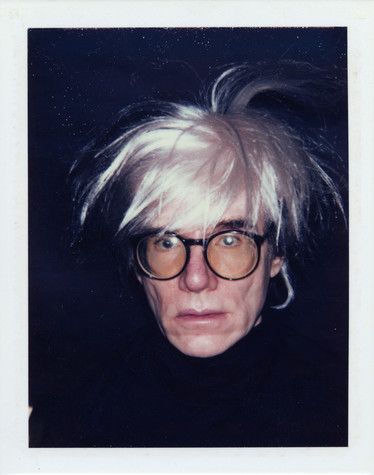 A photograph of Andy Warhol wearing large, round glasses and a black turtleneck that blends in with the black background. His white wig is tossed and hair sticks out in all directions.