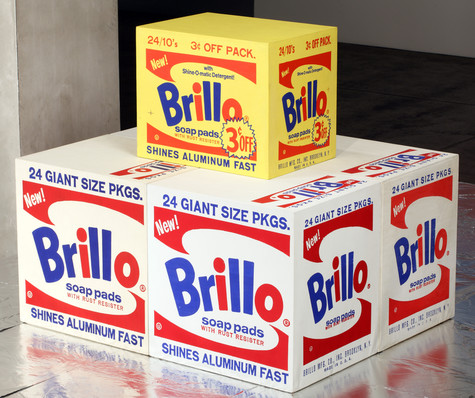 Four white boxes with the red and blue Brillo soap pads logo on them sit on a silver floor. On top of them is a smaller, yellow box with the same design and a sticker boasting that it is 3 cents off.