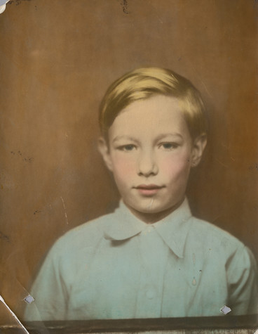 A photograph of Andy Warhol as a child. He wears a pale blue button up shirt and stands against a solid brown background. His hair is faintly gold, and there is a tint of pink to his cheeks and lips.