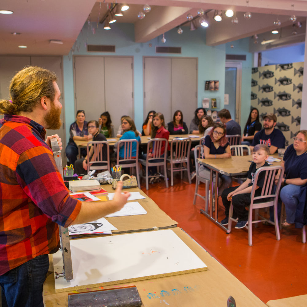 A male artist educator with long blond hair pulled back into a bun wearing a red plaid shirt presents information to students sitting in silver chairs at long, rectangular tables in the Andy Warhol Museum's studio.