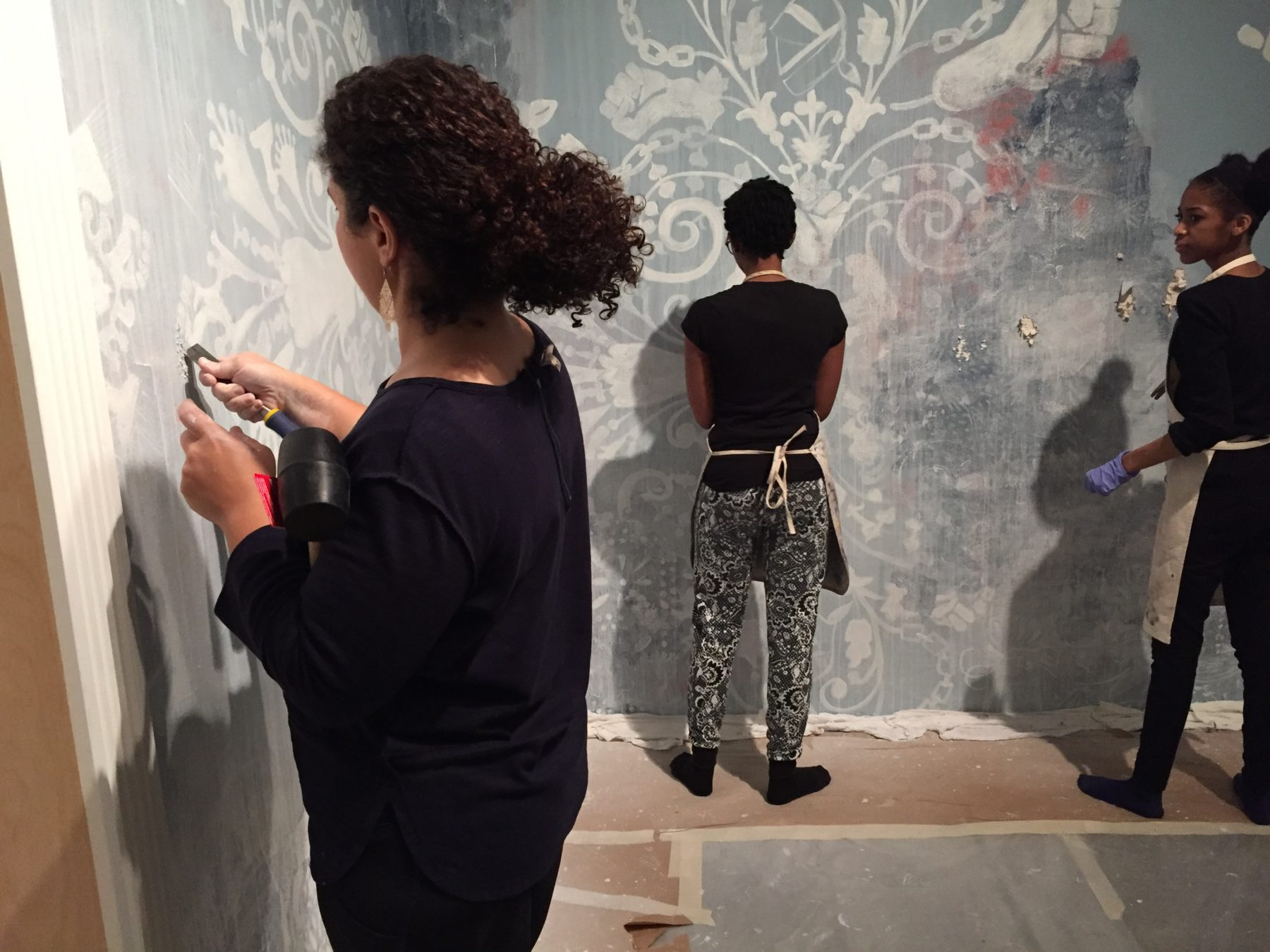 A group of volunteers help artist Firelei Baez scrape paint off a wall in her exhibition gallery.
