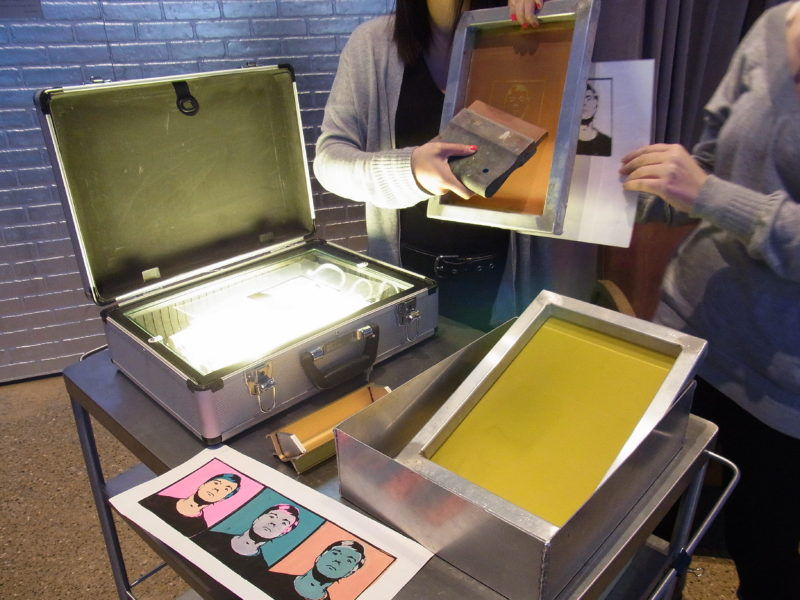 An artist educator holds up a screen and a squeegee to explain the print making process in the Andy Warhol Museum lobby.