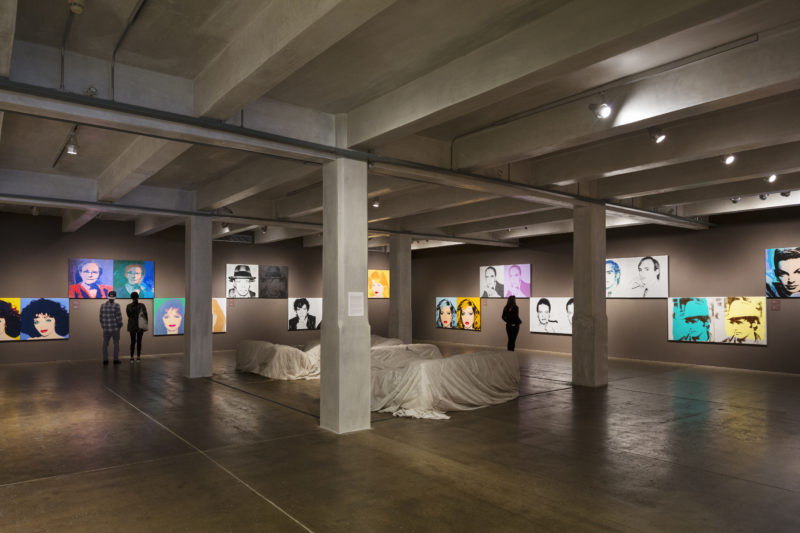 A photograph of a gallery with cement floors and grey walls that are covered in large pairs of screen-printed portraits. Four pillars in the center of the room surround a few pieces of furniture draped in white fabric.