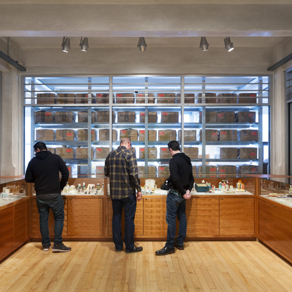 Three men examine artifacts in the Andy Warhol Museum Archives. Three walls of the room have glass cases, and through the glass wall rows and rows of the cardboard boxes that are Andy Warhol's time capsules are visible.