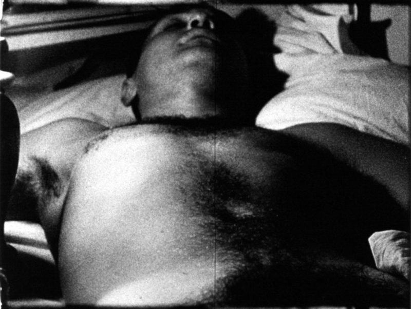 A still from one of Warhol's black and white films featuring a shirtless man lying on his back, asleep.