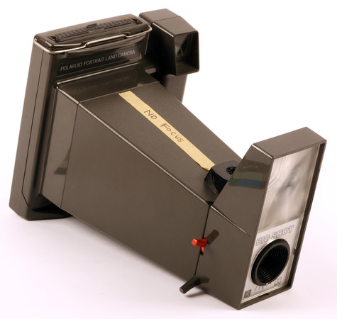 A Polaroid camera with a piece of tape on its side that reads No Focus.