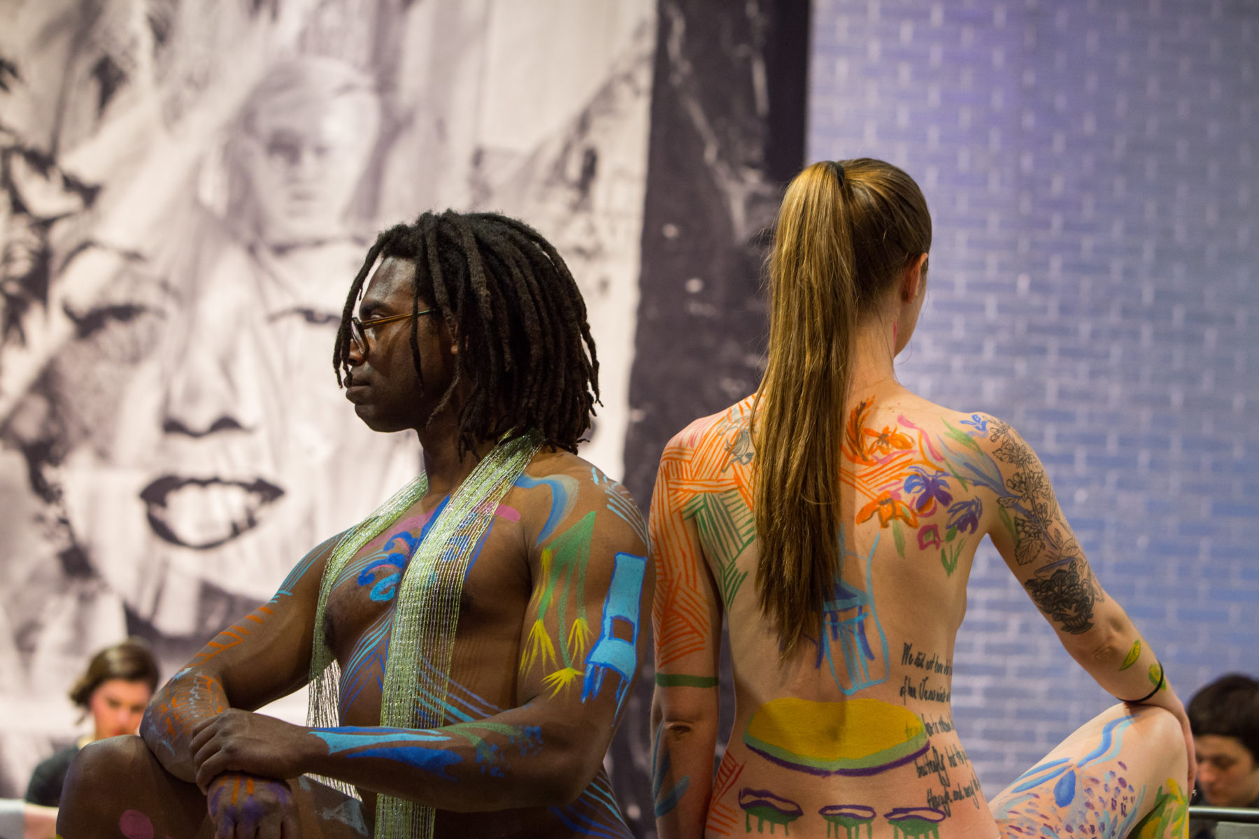 Two models posing in The Warhol entrance space. The model on the left is an African-American man, right hand resting on his propped up knee, his left hand grabbing his right wrist. He is standing back to back with a Caucasian woman, her left arm by her side and right hand grabbing her right propped up knee. Both models have a variety of small pictures painted on them with colorful body paint.
