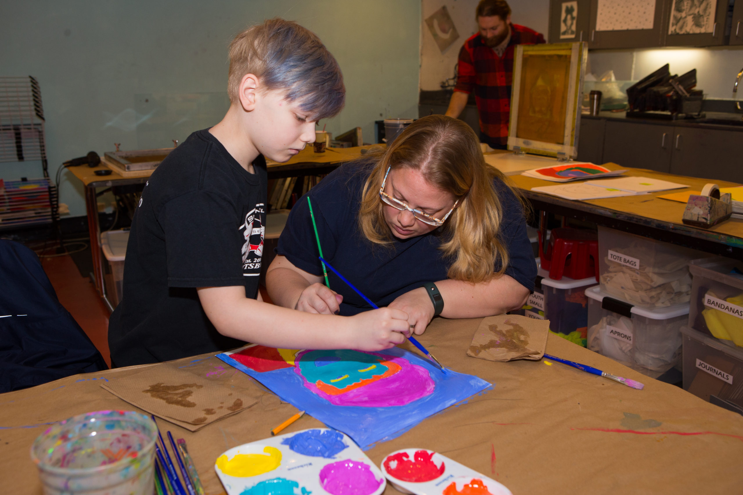 A child and an adult work on a Warhol-inspired painting in The Factory, the museum's underground studio.