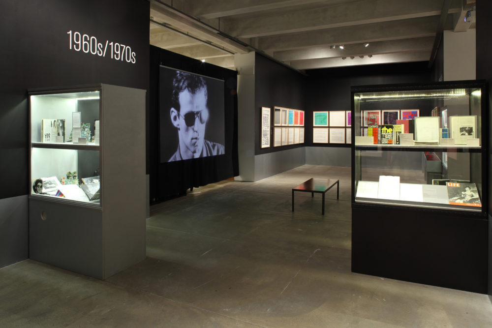 A gallery featuring a screen playing a screen test, several rows of pictures hanging on the walls, and a few glass display cases filled with archival material.