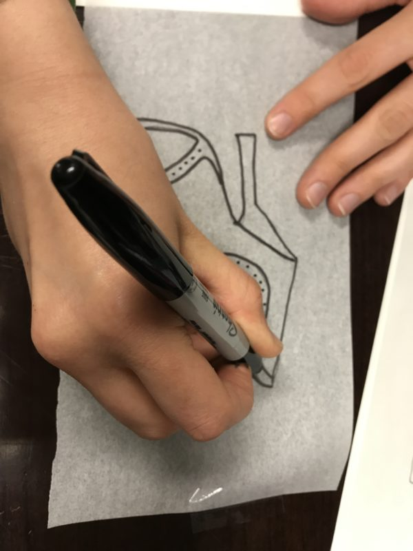 A pair of hands re-traces the outline of a shoe on tracing paper with a black Sharpie marker.