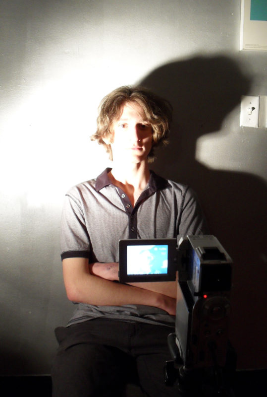 A young man sits with his arms crossed over his abdomen in front of a video camera. He has a slim build and shaggy light brown hair, and is wearing a short-sleeved gray polo shirt and gray trousers. A bright light from the left is shining on his face, partially obscuring his facial features while creating strong shadows to the right. A light switch can be seen on the wall behind him to the right of his head.