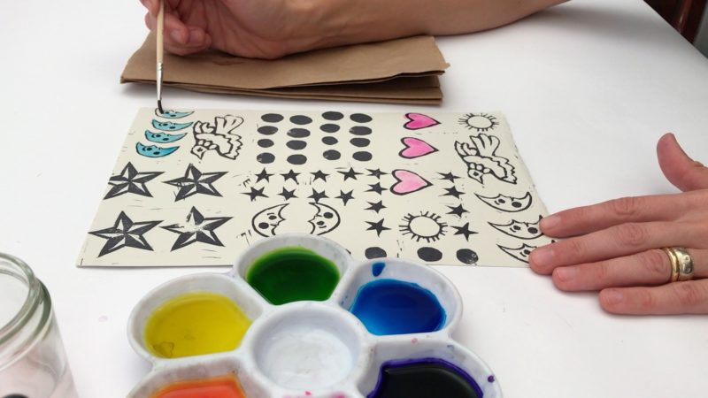 With several different designs stamped on a piece of paper, the student uses watercolor paints to fill in some of the images. Some of the hearts have been filled in pink, and the student is painting the crescent moon designs blue.