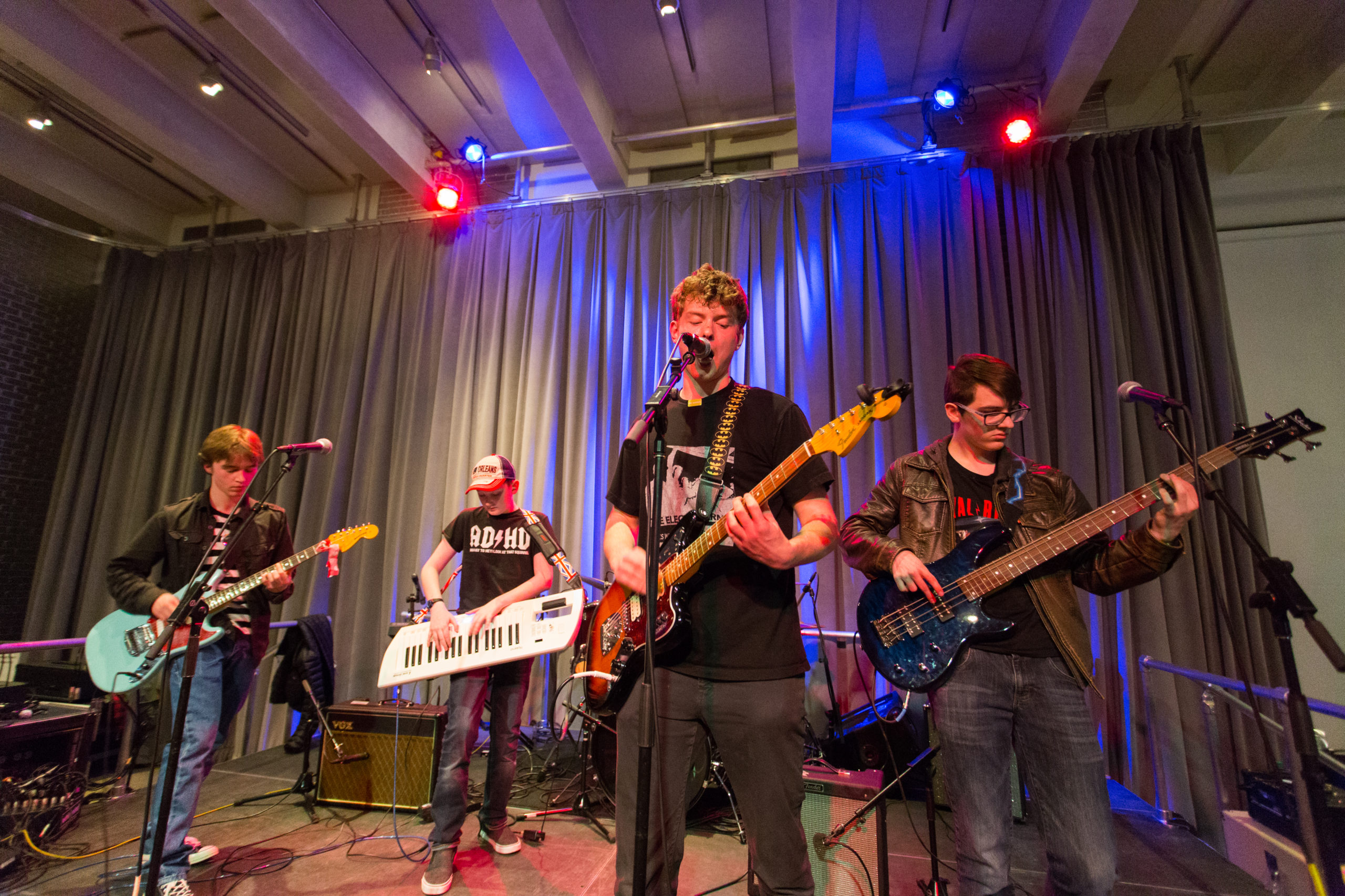 Four young male musicians perform on stage. Each one holding a different instrument - guitar, keytar, guitar and bass.