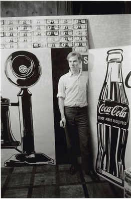 A black and white photo of Andy Warhol, wearing dark pants and al light button-down shirt, standing in his study beside two paintings, one of a telephone and one of a coca cola bottle, each approximately as tall as he is.