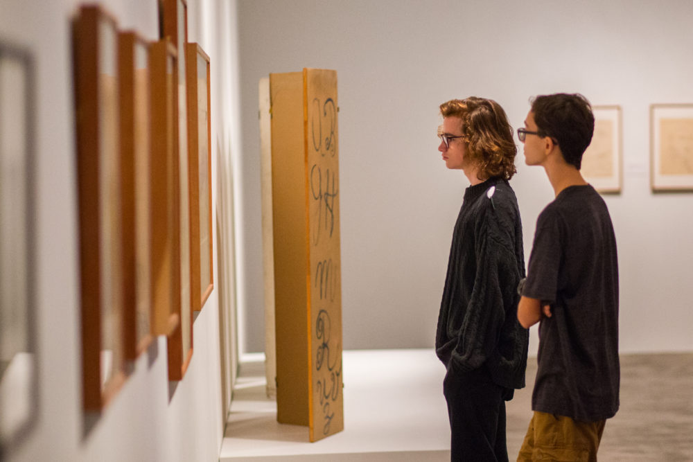 Two young men look at artwork in a gallery