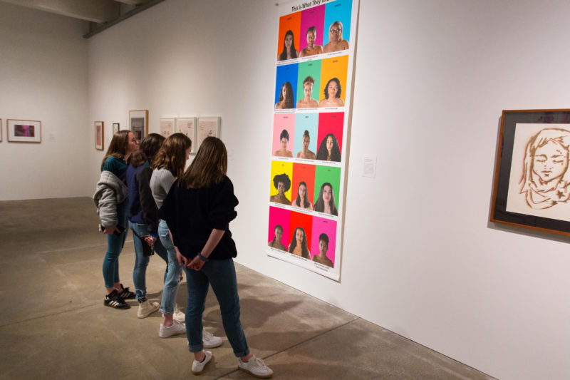 A group of girls stand together to look at large artwork on gallery wall.