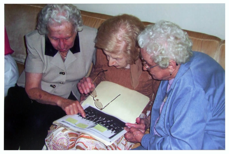 Three women huddled around an image, working to identify who is in a photo.
