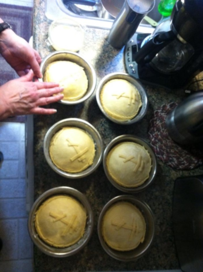 Photo of hands making a loaf of paska, next to five more loaves of paska, in dough form, ready to be baked.