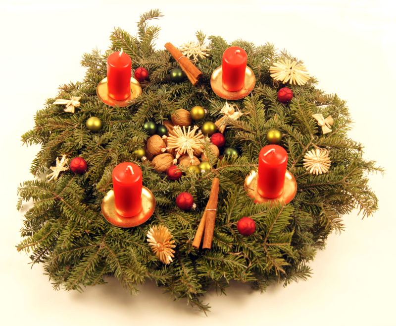 Image of advent wreath with unlit red candles and red and gold ornaments.