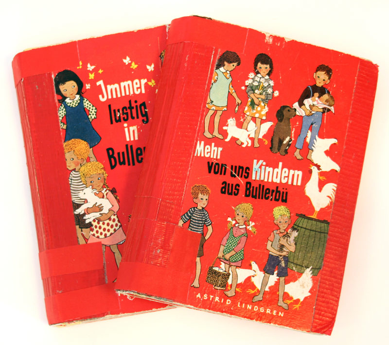 Front view of two red children's books. The titles are in German and are surrounded by images of children and various animals.
