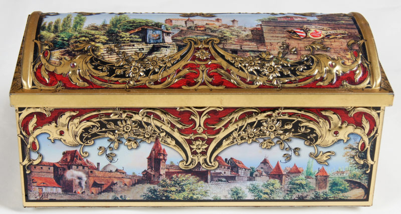 Front view of a closed tin box with ornate gold embellishment and a painted village.