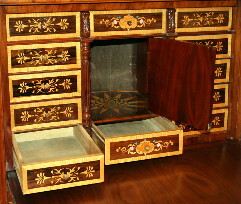 The boxes that make up the design of the desk's backing are opened, revealing that each box is a secret compartment. The rectangular boxes become drawers that extend outward, and the square box opens to become a miniature storage space.