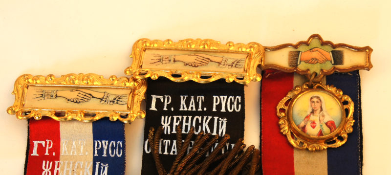 Close-up view of the top halves of three insignias. The insignias are topped with images of shaking hands