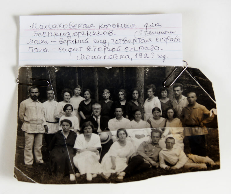 Front view of a black and white photograph paperclipped to an index card with a note hand-written in Russian. The photograph features three rows of men and women posing for the camera in front of trees.