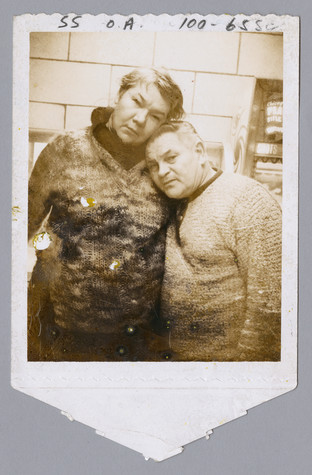A faded, sepia-toned polaroid picture of a woman with short hair on the left resting her head on a shorter man with dark hair to the right.