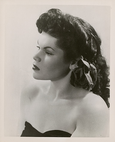 A black and white publicity photo of a person in a dark dress with long, dark hair, wearing makeup and looking off to the left of the frame.