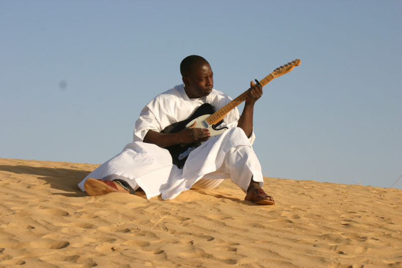 A person dressed in white, sits outside on sand in the daylight while playing guitar.