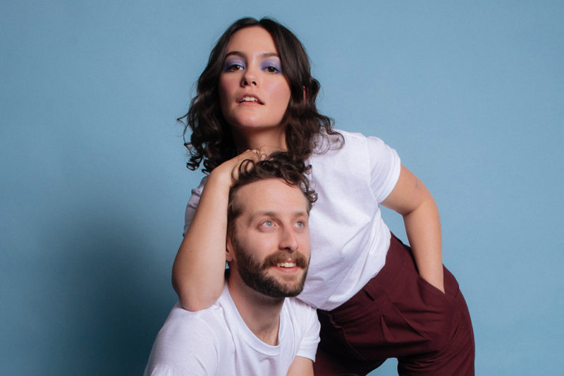 Two people are in front of a light blue background. One is standing over the other with their elbow on top of the other's shoulder and hand on top of their head.