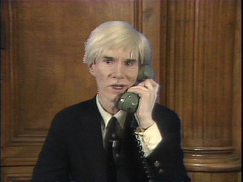 A video still of a person with light hair and wearing a dark suit talking on a green telephone.