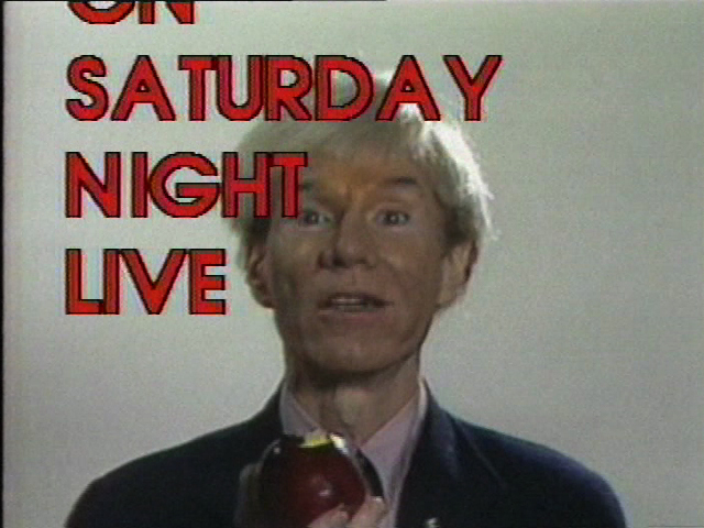 A video still of a person holding an apple and looking towards the camera. A Saturday Night Life graphic in red, capital letters appears in the foreground.