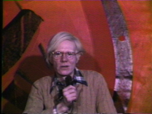 Film still of a person holding a mic in front of a red background. He is shown here with a pair of round glasses, wearing a black and white plaid shirt underneath a brown sweater.