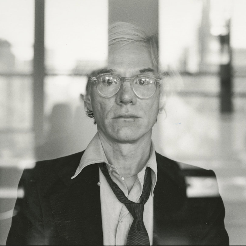 Warhol, standing behind a glass window, looks out at the viewer.