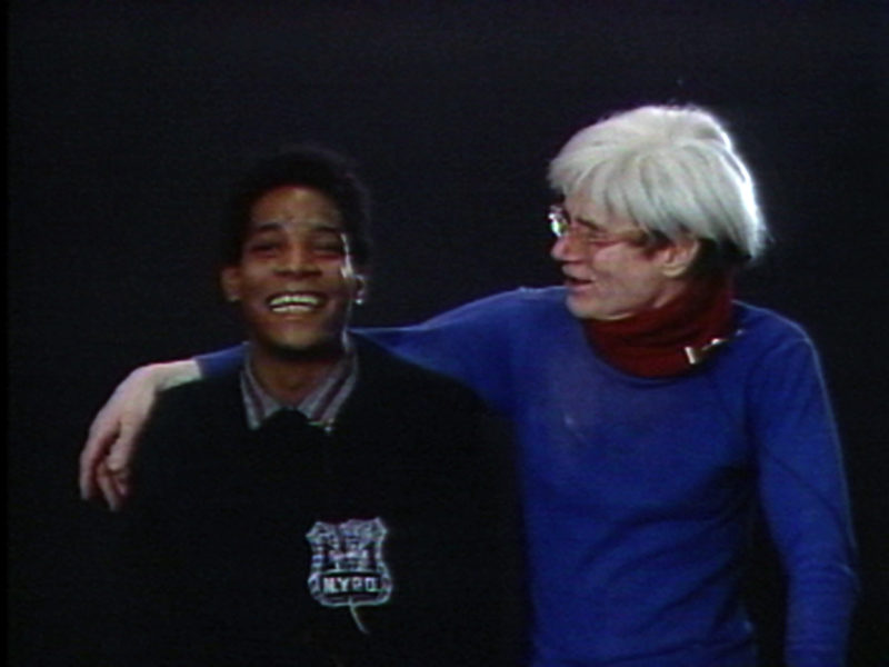 Jean-Michel Basquiat faces forward and smiles as Andy Warhol drapes his arm over his shoulders and looks at him