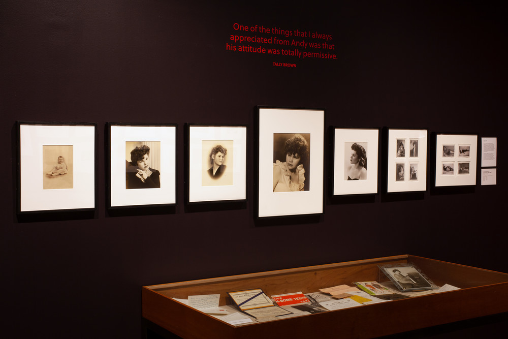 A single row of framed photographs of Tally Brown hang on a dark wall