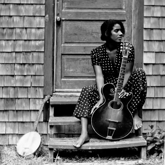 Woman with guitar sits on the steps of a cottage with weathered split-shake shingles.